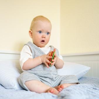 Baby, das mit magnetischem konstruktionsspielzeug spielt, während es auf dem bett sitzt
