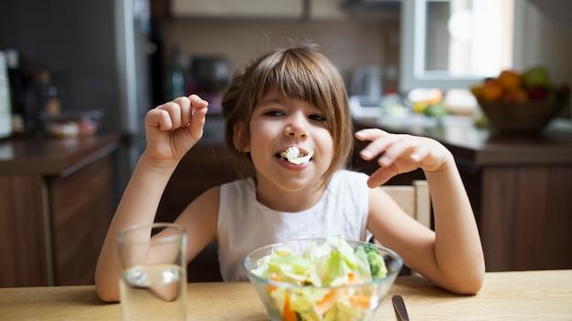Baby, das mit salat beim essen spielt