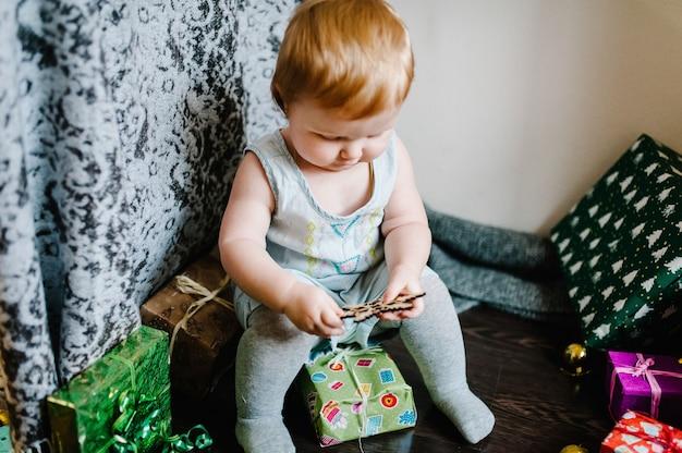 Baby, das mit spielzeug spielt, sitzt auf den hintergrundgeschenken