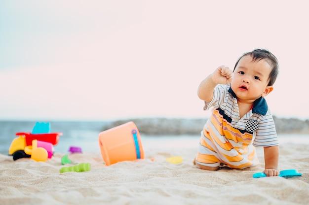 Baby, das mit strandspielzeug mit seiner mutter am tropischen strand spielt.