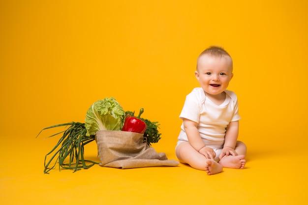 Baby, das mit tasche des gemüses auf gelb sitzt
