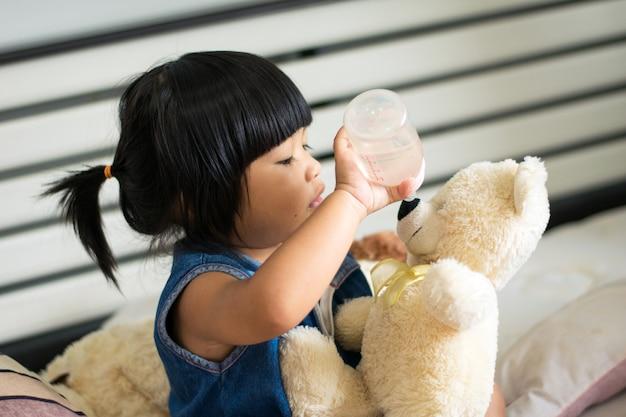 Baby, das trinkmilch des teddybären auf bett spielt