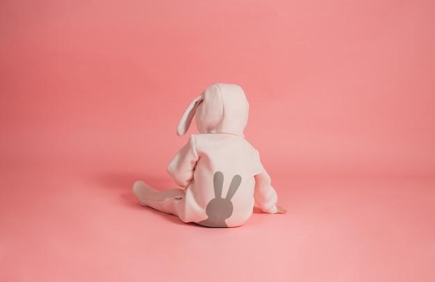 Baby, das zurück im häschenkostüm auf rosa hintergrund sitzt