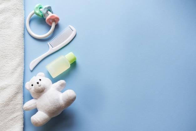 Baby-dusche lag flach auf blau. kinderspielzeug und shampoo.