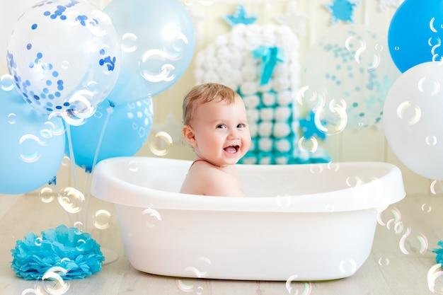 Baby feiert geburtstag in einem bad mit luftballons