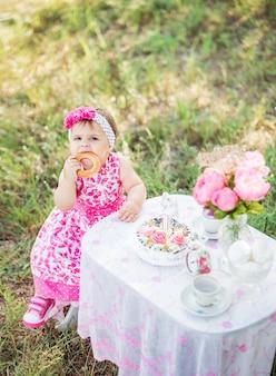 Baby feiert ihren ersten geburtstag mit kuchen und luftballons in der natur