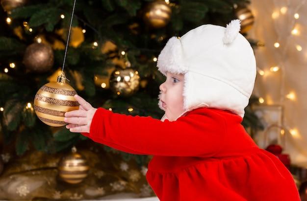 Baby greift nach einem weihnachtsbaumball. süßes kleines mädchen in einem roten kleid und weißem hut drückt gefühle aus. weihnachtskonzept mit kleinem kind