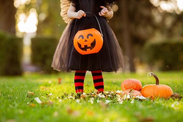 Baby hält ein kürbisförmiges café für halloween, nahaufnahme, platz für text