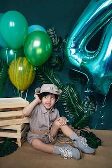 Baby hält einen ballon zu hause auf einem grünen hintergrund an seinem geburtstag
