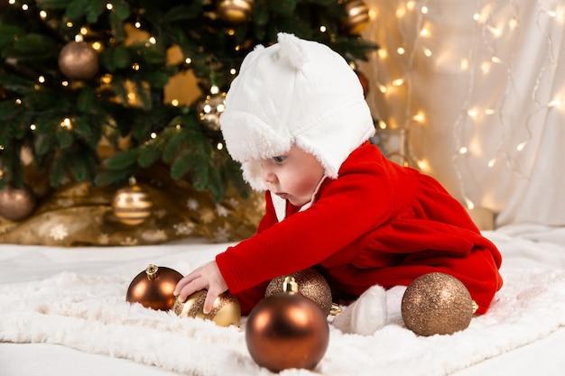 Baby halten weihnachtsball. süßes kleines mädchen in einem roten kleid und weißem hut drückt gefühle aus. weihnachtskonzept mit kleinem kind