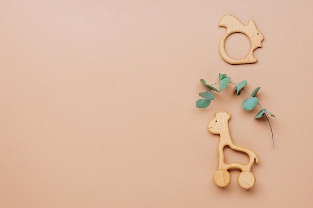Baby holzspielzeug eichhörnchen und giraffe auf beigem hintergrund mit leerzeichen für text. draufsicht, flach liegen.