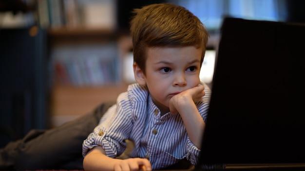 Baby im blauen hemd, das auf laptop beobachtet