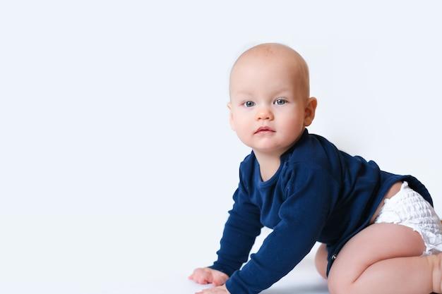 Baby im blauen hemd und in der windel, die kriechen