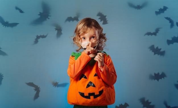Baby im karnevalskürbiskostüm, das stilles zeichen zum betrachter bei halloween-party macht.