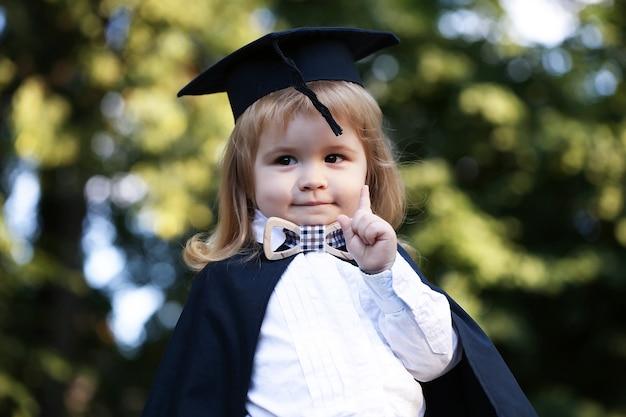 Baby im kleinen outdoor-jungenkind des mantels im schwarzen akademischen kleid und im quadratischen schulhut und in der fliege, die draußen auf grünem natürlichem stehen