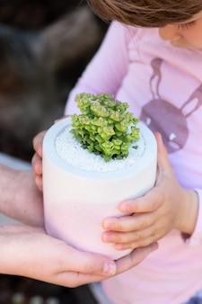 Baby im lila pullover hält eine saftige pflanze im keramischen lila-weißen blumentopf mit ihren händen