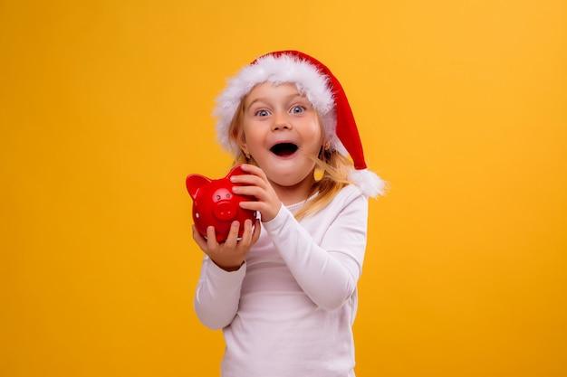Baby im sankt-hut, der rotes sparschwein auf gelber wand, raum für text hält