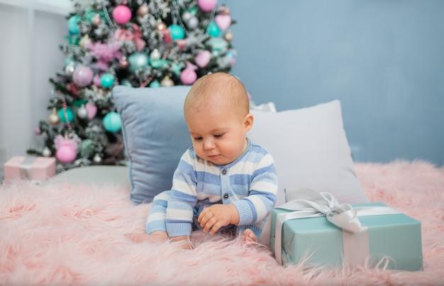 Baby im schlafanzug, der auf einer pelzdecke mit einem geschenk auf mit weihnachtsbaum sitzt