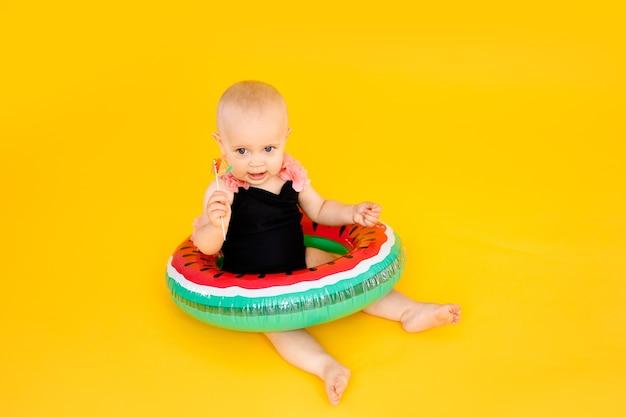 Baby im schwarzen und rosa badeanzug, der aufblasbaren poolschwimmer der wassermellone hält