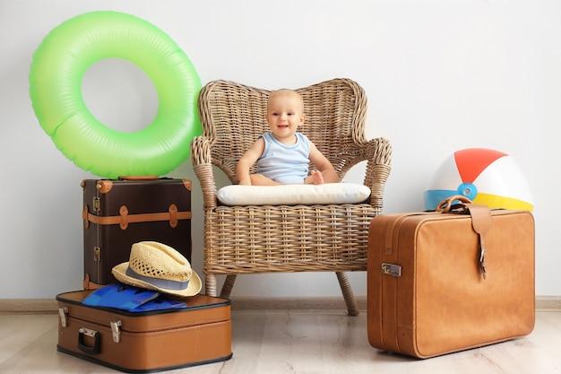 Baby im sessel mit koffern