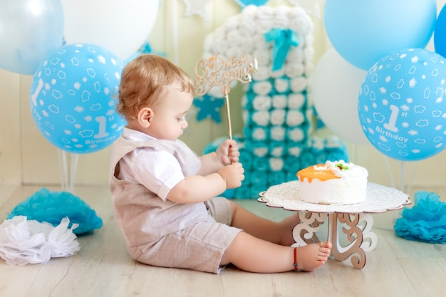 Baby im studio mit einem kuchen und luftballons