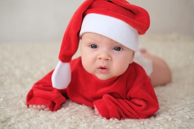 Baby im weihnachtsmannkostüm auf weiß