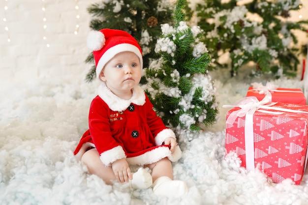 Baby im weihnachtsmannkostüm, das nahe weihnachtsbaum sitzt. familienurlaubskonzept.