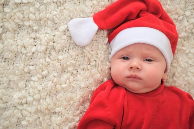 Baby im weihnachtsmannkostüm. weihnachtskleinkind in der weihnachtsmütze. baby in rotem kostüm und hut