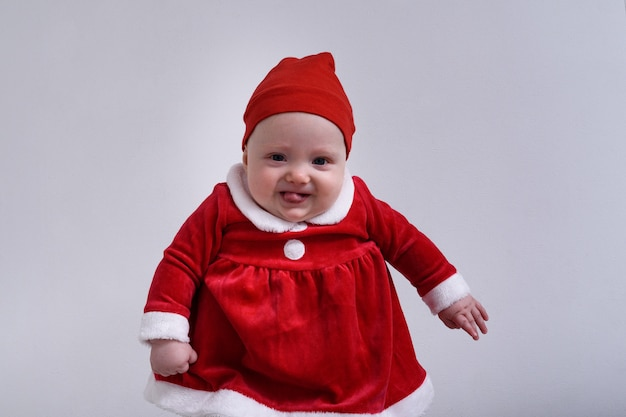 Baby im weihnachtsmannkostüm zeigt zunge.