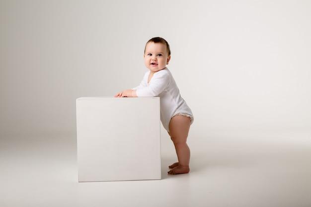 Baby im weißen body steht auf einem weißen würfel an einer hellen wand gelehnt