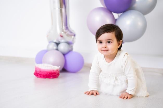Baby im weißen kleid, das auf dem boden sitzt und ihren ersten geburtstag mit kuchen und luftballons feiert.