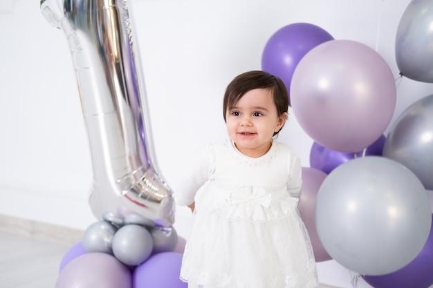Baby im weißen kleid, das ihren ersten geburtstag mit kuchen und luftballons feiert.