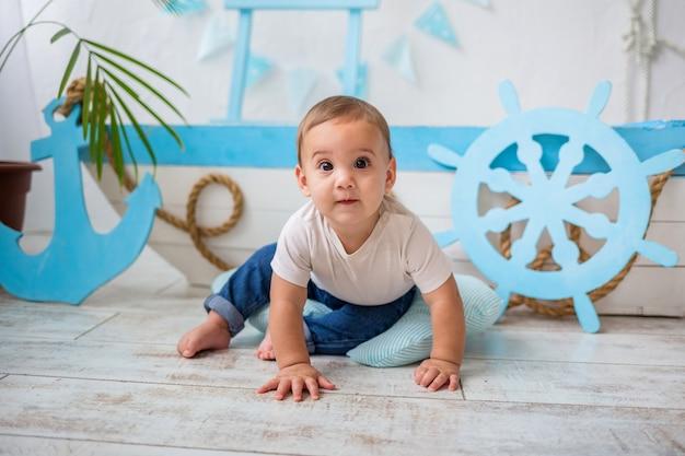 Baby im weißen t-shirt und in den jeans, die auf einem hölzernen boot sitzen