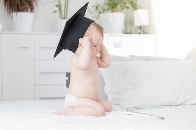 Baby in abschlusskappe mit blick auf digitales tablet