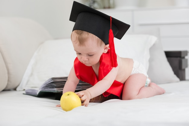 Baby in abschlusskappe posiert mit apfel und großem buch
