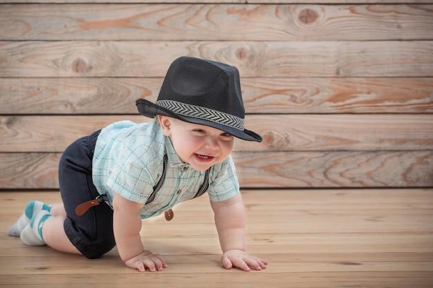 Baby in den schwarzen hut-, hemd- und hosenträgershorts auf hölzernem hintergrund