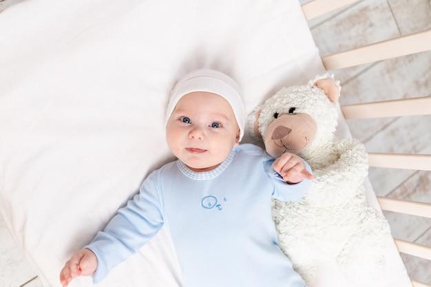 Baby in der krippe, porträt eines niedlichen babys 3 monate in der krippe mit einem teddybärspielzeug, kinder und geburtskonzept