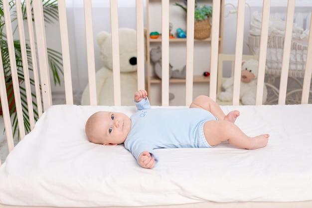 Baby in der krippe, süßer kleiner junge von sechs monaten, der im kinderzimmer auf dem bett liegt