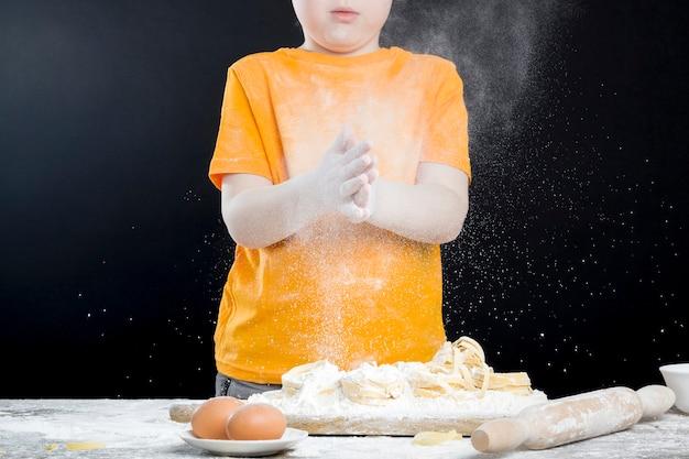 Baby in der küche beim helfen beim zubereiten von essen, junge mit roten haaren und schönen gesichtszügen