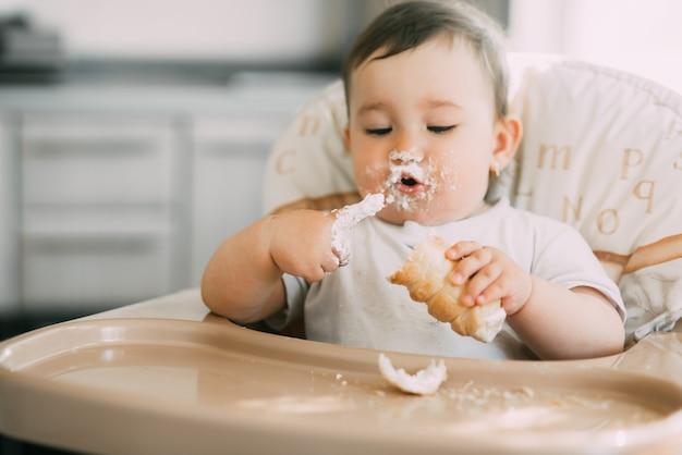 Baby in der küche eifrig die leckeren sahnehörner essen, gefüllt mit einer vanillecreme sehr lustig