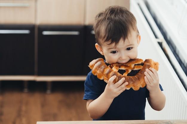 Baby in der küche isst ein großes brötchen oder einen kuchen mit schokolade eating