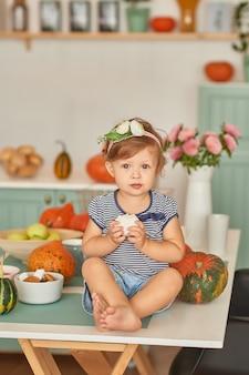 Baby in der küche mit thanksgiving-dekorationen