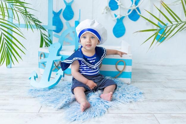 Baby in der seezone mit einem schiff in einer seemannsweste, das konzept der sommerferien