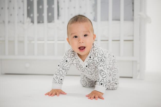 Baby in einem babybett auf einem hellen hintergrund