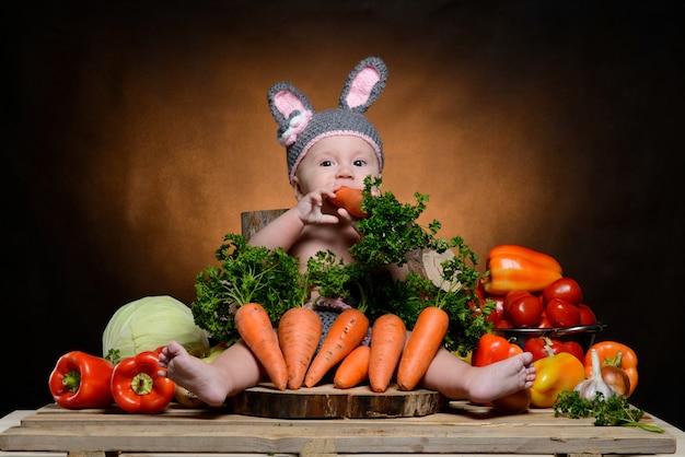 Baby in einem kaninchenkostüm mit gemüse auf einem holz