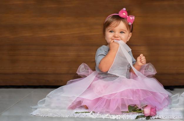 Baby in einem kleid und bändern auf einem hölzernen hintergrund. ein kind in einem rosa kleid beißt ein weißes band auf einem hölzernen hintergrund
