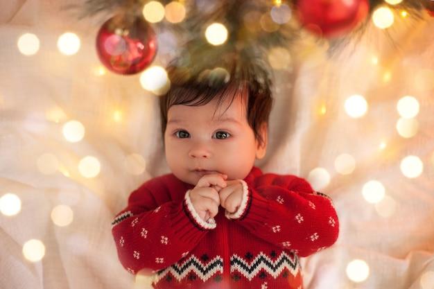 Baby in einem roten pullover, der kamera unter einem weihnachtsbaum mit kugeln und einer girlande an weihnachten schaut
