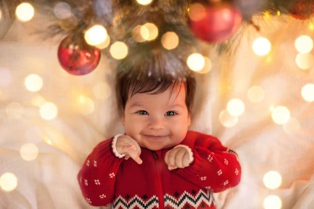 Baby in einem roten pullover, der unter einem weihnachtsbaum mit kugeln und einer girlande an weihnachten lächelt