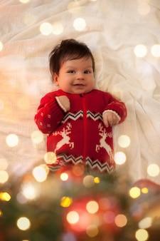 Baby in einem roten pullover liegt unter einem weihnachtsbaum mit kugeln und einer girlande zu weihnachten. bild mit bokeh-lichtern.