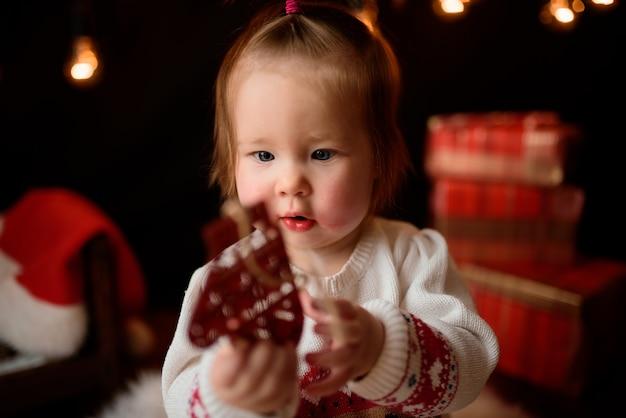 Baby in einem roten weihnachtskostüm mit retro-girlanden sitzt auf einem fell